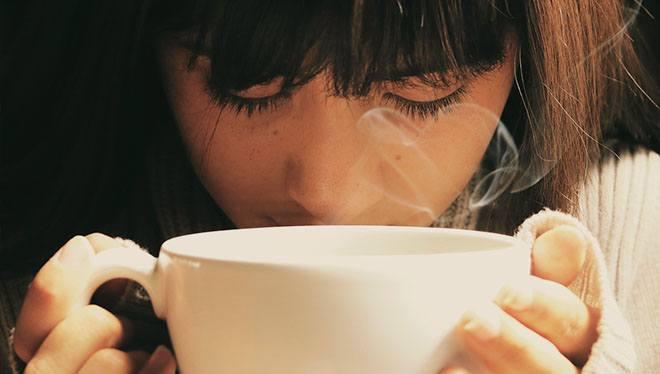 девушка вдыхает аромат кофе