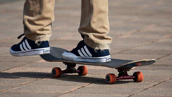 парень отталкивается от земли на скейте