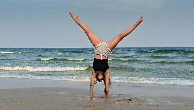 девушка делает колесо на фоне моря
