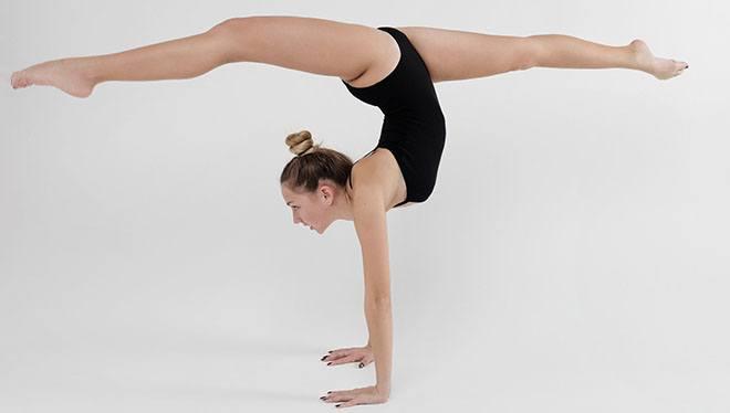 гимнастка делает шпагат на руках