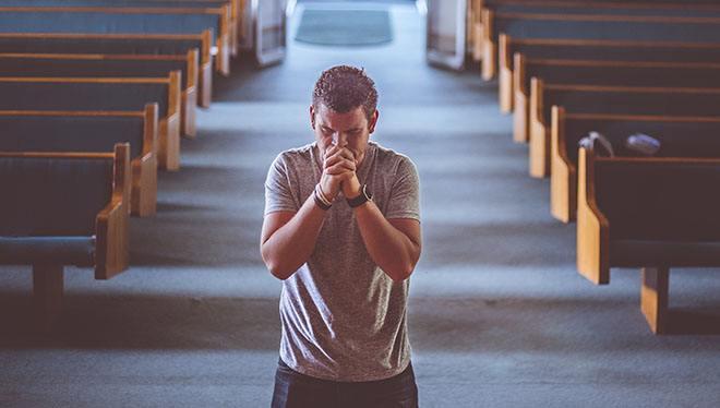 мужчина молится в церкви на коленях