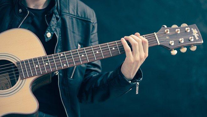 гриф гитары в руках девушки