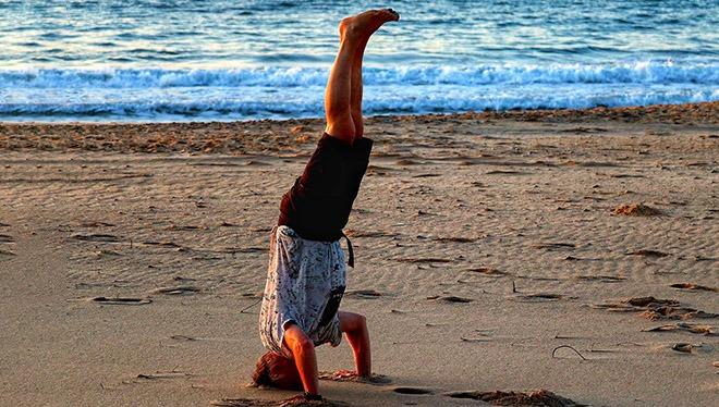 мужчина на пляже на голове
