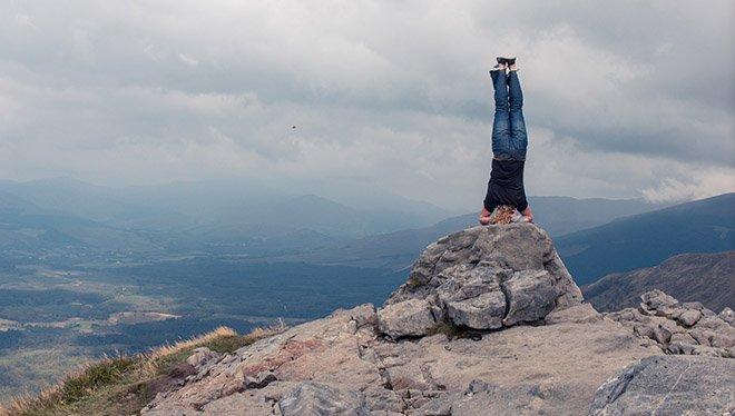 мужчина стоит на руках поверх камня