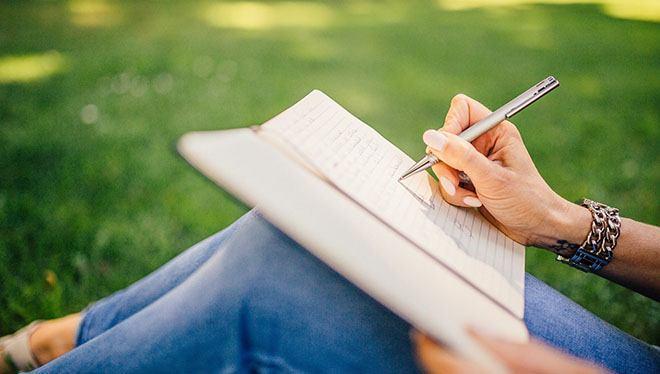 девушка пишет в тетради на природе