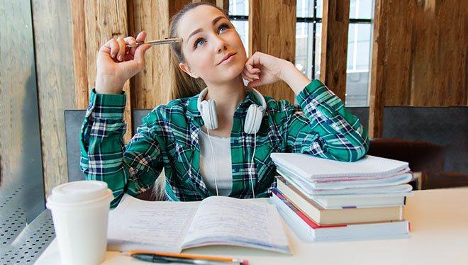 студентка пишет в тетради и думает