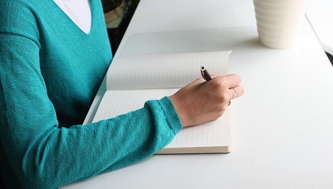 женщина пишет в блокнот за столом