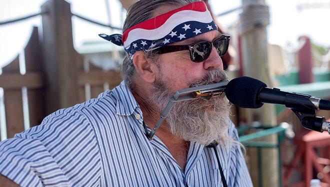 бородатый музыкант играет на гармонике