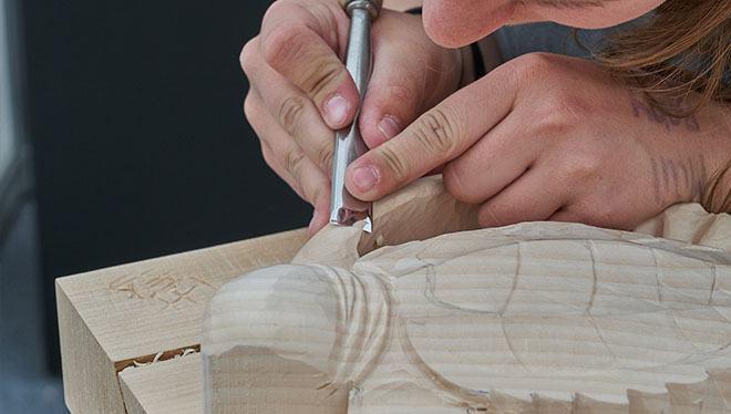 девушка вырезает фигурку из дерева