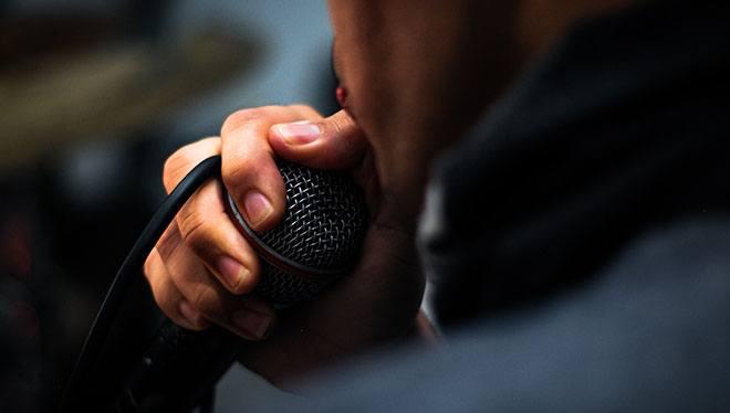 мужчина держит у губ микрофон